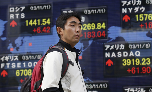A man walks past and electronic stock board of a securities firm showing Japan's benchmark Nikkei 225, top center, that gained 183.04 points, or 1.30 percent, and closed at 14,269.84 in Tokyo, Monday, Nov. 11, 2013. Asian stock markets made a lackluster start to the week after unexpectedly strong U.S. economic growth and hiring reinforced expectations that the Federal Reserve will start cutting back stimulus soon. Stocks in Manila sank after a typhoon devastated the eastern Philippines, killing thousands of people. (AP Photo/Shizuo Kambayashi)