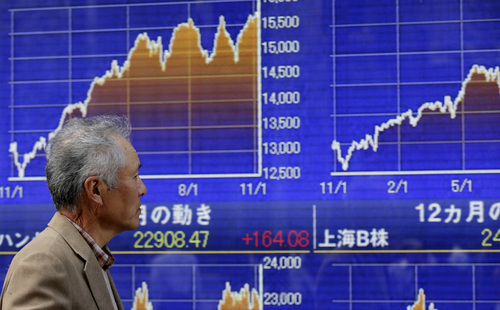 A man walks past and electronic stock board of a securities firm in Tokyo, Monday, Nov. 11, 2013. Asian stock markets made a lackluster start to the week after unexpectedly strong U.S. economic growth and hiring reinforced expectations that the Federal Reserve will start cutting back stimulus soon. (AP Photo/Shizuo Kambayashi)