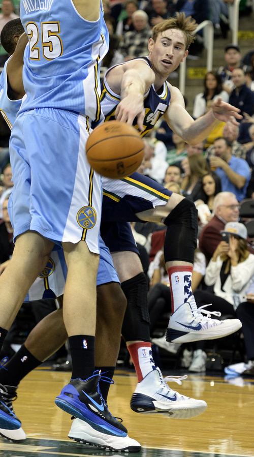 Rick Egan  | The Salt Lake Tribune   Utah Jazz shooting guard Gordon Hayward (20) tosses a pass around Denver Nuggets center Timofey Mozgov (25), in NBA action, Utah vs. The Denver Nuggets, in Salt Lake City, Monday, November 11, 2013.