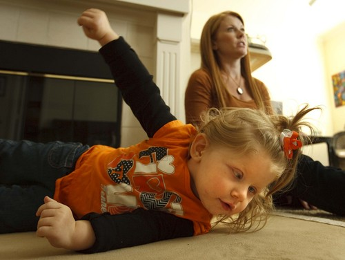Leah Hogsten  |  The Salt Lake Tribune Piper Koozer tries rolling onto her stomach on the floor of her new Colorado apartment. Her parents, Tennesseans Annie and Justin Koozer relocated in order to obtain a cannabis oil that has proven effective at calming intractable seizures.
