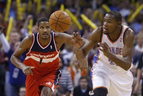 Washington Wizards forward Trevor Ariza (1)  and Oklahoma City Thunder forward Kevin Durant (35) chase a loose ball after Durant blocked a shot by Ariza in overtime  of an NBA basketball game in Oklahoma City, Sunday, Nov. 10, 2013. Oklahoma City won 106-105 in overtime. (AP Photo/Sue Ogrocki)