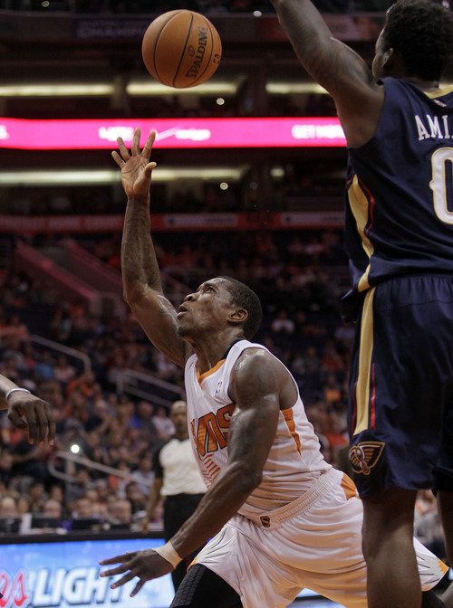 Phoenix Suns guard Eric Bledsoe (2), left, scores on New Orleans Pelicans forward Al-Farouq Aminu (0) in the third quarter during an NBA basketball game on Sunday, Nov. 10, 2013, in Phoenix. The Suns defeated the Pelicans 101-94. (AP Photo/Rick Scuteri)