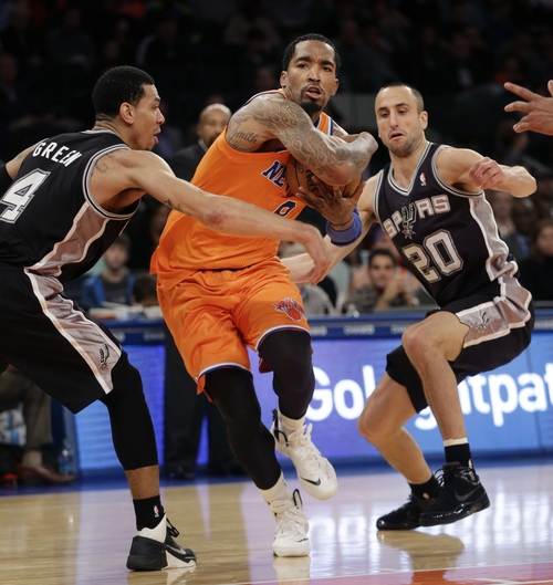 New York Knicks' J.R. Smith, center, drives through San Antonio Spurs' Danny Green, left, and Manu Ginobili during the second half of an NBA basketball game at Madison Square Garden, Sunday, Nov. 10, 2013, in New York. The Spurs won 120-89. (AP Photo/Seth Wenig)