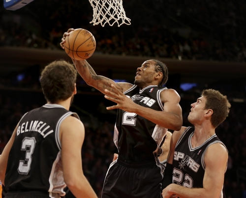 San Antonio Spurs' Kawhi Leonard, center, grabs a rebound over teammates Marco Belinelli, left, and Tiago Splitter during the second half of an NBA basketball game against the New York Knicks at Madison Square Garden, Sunday, Nov. 10, 2013, in New York. The Spurs won 120-89. (AP Photo/Seth Wenig)