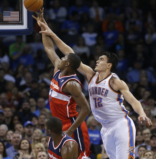 Oklahoma City Thunder center Steven Adams (12) and Washington Wizards center Kevin Seraphin (13) reach for a rebound in the second quarter of an NBA basketball game in Oklahoma City, Sunday, Nov. 10, 2013. (AP Photo/Sue Ogrocki)