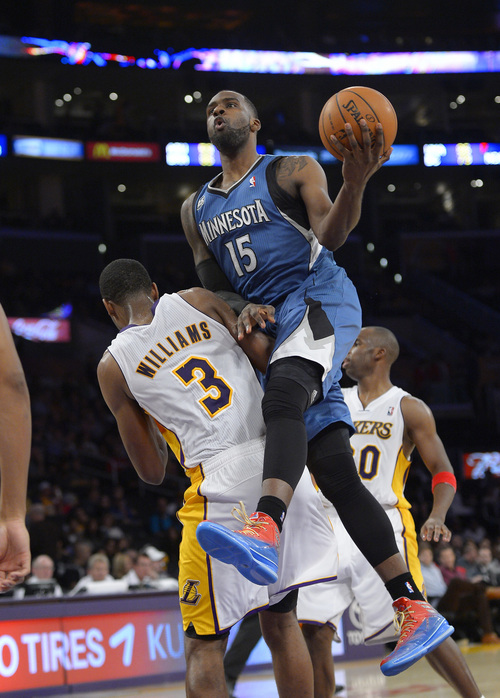 Minnesota Timberwolves forward Shabazz Muhammad, right, puts up a shot as Los Angeles Lakers forward Shawne Williams defends during the second half of an NBA basketball game, Sunday, Nov. 10, 2013, in Los Angeles. (AP Photo/Mark J. Terrill)