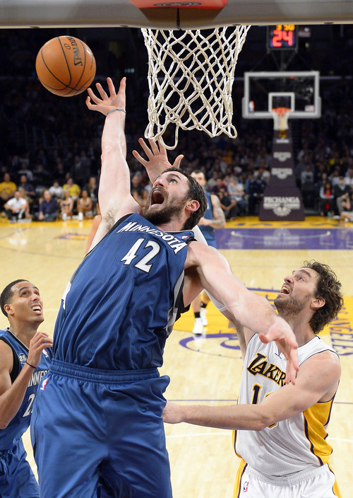 Minnesota Timberwolves forward Kevin Love, left, goes after a rebound along with Los Angeles Lakers center Pau Gasol, of Spain, during the first half of an NBA basketball game Sunday, Nov. 10, 2013, in Los Angeles. (AP Photo/Mark J. Terrill)