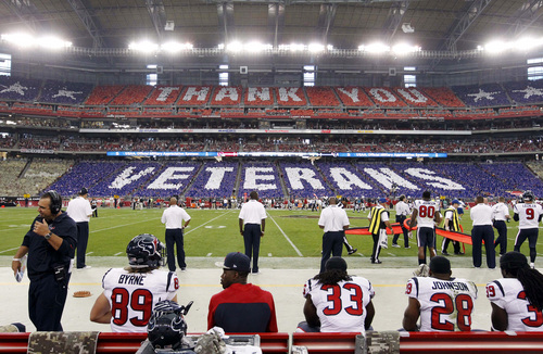 """Fans hold flip cards from their seats thanking veterans during the first half of an NFL football game between the Houston Texans and the Arizona Cardinals, Sunday, Nov. 10, 2013, in Glendale, Ariz. The NFL is celebrating Veterans Day with a league wide """"Salute to Service"""" campaign. (AP Photo/Ross D. Franklin)"""