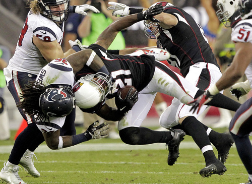 Houston Texans strong safety D.J. Swearinger, second from left, tackles Arizona Cardinals cornerback Patrick Peterson (21) during a punt return in the second half of an NFL football game Sunday, Nov. 10, 2013, in Glendale, Ariz. (AP Photo/Rick Scuteri)
