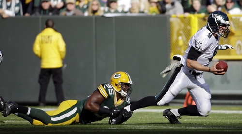 Green Bay Packers' Datone Jones tackles Philadelphia Eagles quarterback Nick Foles during the first half of an NFL football game Sunday, Nov. 10, 2013, in Green Bay, Wis. (AP Photo/Morry Gash)
