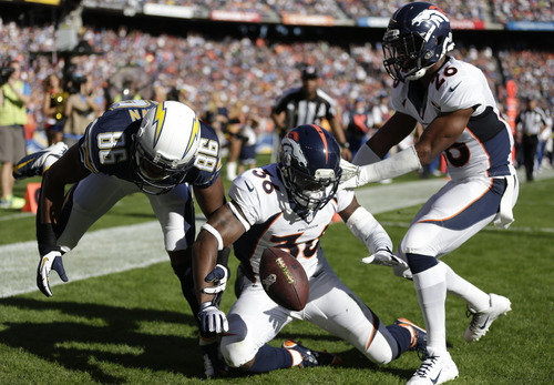 San Diego Chargers wide receiver Vincent Brown, left, tries to grab a dropped ball along with Denver Broncos cornerback Kayvon Webster, center, and free safety Rahim Moore, right, during the second half of a NFL football game Sunday, Nov. 10, 2013, in San Diego. (AP Photo/Gregory Bull)