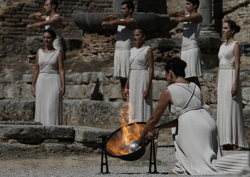 Actress Ino Menegaki as high priestess, lights the Olympic Flame from the sun's rays, during the lighting of the Olympic flame at Ancient Olympia, in west southern Greece on Sunday  Sept. 29, 2013. Using the sun's rays at the birthplace of the ancient Olympics, organizers carried out a successful ceremony to light the flame for the 2014 Sochi Winter Olympics Feb. 7-23, 2014 in Russia. (AP Photo (AP Photo/Dimitri Messinis)