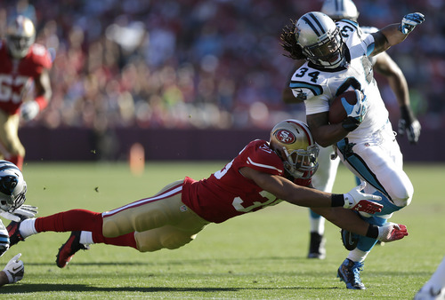 Carolina Panthers running back DeAngelo Williams (34) runs past San Francisco 49ers safety Eric Reid (35) to score on a 27-yard touchdown run during the second quarter of an NFL football game in San Francisco, Sunday, Nov. 10, 2013. (AP Photo/Marcio Jose Sanchez)