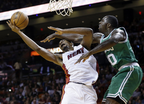 Miami Heat's Chris Bosh, left, attempts to shoot as Boston Celtics' Brandon Bass defends during the first half of an NBA basketball game Saturday, Nov. 9, 2013, in Miami. (AP Photo/Lynne Sladky)