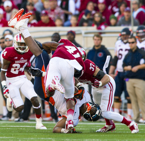 Illinois' Jon Davis (3) is thrown to the turf by Indiana's Clyde Newton (41) during the first half of an NCAA college football game, Saturday, Nov. 9, 2013, in Bloomington, Ind. (AP Photo/Doug McSchooler)