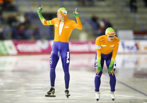 Sven Kramer, left, of the Netherlands, celebrates the team's new World record as teammate Jan Blokhuijsen, catches his breath following the men's team pursuit competition at the World Cup speed skating event in Calgary, Alberta, Saturday, Nov. 9, 2013.  The Netherlands had a time of 3:37.17, breaking the mark of 3:37.80 set in Salt Lake City in 2007. (AP Photo/The Canadian Press, Jeff McIntosh)