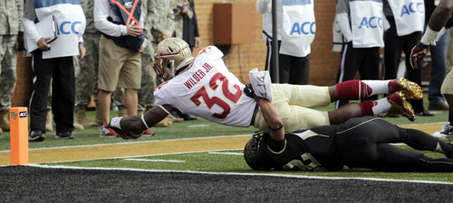 Florida State running back James Wilder Jr. (32)  reaches across the goal line to score against Wake Forest defenders in the first half of an NCAA college football game in Winston-Salem, N.C., Saturday, Nov. 9, 2013. (AP Photo/Nell Redmond)