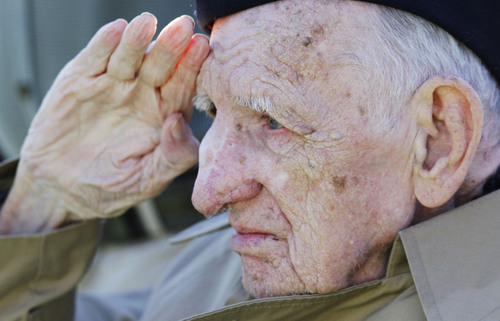 Jesse Beazley of Nicholasville, Ky., a World War II veteran and D-Day survivor salutes the flag during the national anthem on Hero's Day before an NCAA college football game between Kentucky and Missouri, Saturday, Nov. 9, 2013, in Lexington, Ky. (AP Photo/James Crisp)