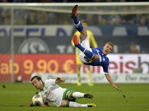 Schalke's Max Meyer, up, is fouled by Bremen's Luca Caldirola of Italy during the German  Bundesliga  soccer match between FC Schalke 04 and Werder Bremen in Gelsenkirchen, Germany, Saturday, Nov. 9, 2013. (AP Photo/Martin Meissner)