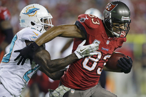Tampa Bay Buccaneers wide receiver Vincent Jackson (83) runs for yardage after a reception as he is tackled by Miami Dolphins free safety Reshad Jones, left, during the first half of an NFL football game in Tampa, Fla., Monday, Nov. 11, 2013.(AP Photo/John Raoux)