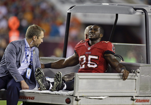 Tampa Bay Buccaneers running back Mike James leaves the field after he was injured during the first half of an NFL football game against the Miami Dolphins in Tampa, Fla., Monday, Nov. 11, 2013.(AP Photo/John Raoux)