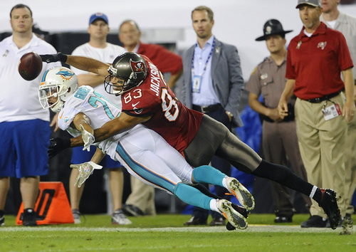 Tampa Bay Buccaneers wide receiver Vincent Jackson (83) reaches for a pass over Miami Dolphins cornerback Brent Grimes (21) during the first quarter of an NFL football game Monday, Nov. 11, 2013, in Tampa, Fla. (AP Photo/Brian Blanco)