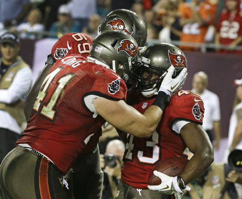 Tampa Bay Buccaneers running back Bobby Rainey, right, celebrates with fullback Erik Lorig (41) and tackle Demar Dotson (69) after scoring a touchdown against the Miami Dolphins on a 1-yard run in the fourth quarter of an NFL football game in Tampa, Fla., Tuesday, Nov. 12, 2013.(AP Photo/John Raoux)