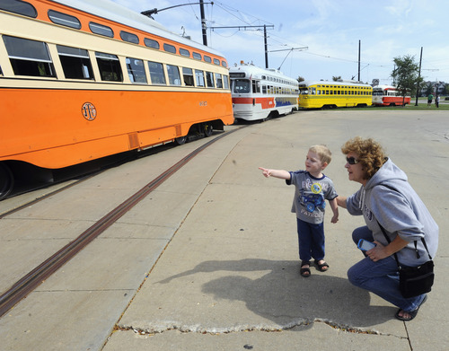 In this Sept. 28, 2013 photo, Johnathan Sainski, 2, of Wheatland, Wis., points out his favorite streetcar to his grandmother Anna Sainski, of Bristol, Wis., during Kenosha Streetcar Day outside the Joseph McCarthy Transit Center in Kenosha, Wis. From left are the Johnstown (Kenosha), Southeastern Pennsylvania, Cincinnati and the Pittsburgh streetcars. When the city of Kenosha lost the auto plant that employed thousands, the a bruised community in southern Wisconsin plucked something unexpected from its pre-automobile past to help reinvent the city and fill its depressed downtown with life. They brought back their street cars, sending brightly colored antique trolleys creeping along a two-mile loop around the city and along the lake Michigan shore. (AP Photo/Michael Schmidt)