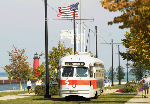 In this Sept. 28, 2013 photo, the Southeastern Pennsylvania streetcar heads west parallel and next to 54th Street during Kenosha Streetcar Day  in Kenosha, Wis. When the city of Kenosha lost the auto plant that employed thousands, the a bruised community in southern Wisconsin plucked something unexpected from its pre-automobile past to help reinvent the city and fill its depressed downtown with life. They brought back their street cars, sending brightly colored antique trolleys creeping along a two-mile loop around the city and along the lake Michigan shore. (AP Photo/Michael Schmidt)