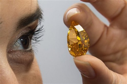 A Christie's employee displays the considered  largest fancy vivid orange diamond in the world, during a press preview in Geneva, Switzerland, Friday, Nov.  1, 2013. The diamond is estimated to fetch US $ 17 million to US $ 20 million, at an auction on Nov. 12, 2013, in Geneva. (AP Photo/Keystone,Martial Trezzini)
