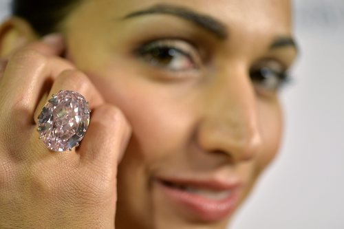 """FILE - In this Sept. 25, 2013 file picture a Sotheby's employee shows The Pink Star diamond weighing 59.6 carat, during a preview at  Sotheby's, in Geneva, Switzerland. The Pink Star, one of the world's natural treasures, is the most valuable diamond ever to be offered at auction, estimated in excess of  US $ 60 million.  It's auction time for the filthy rich again in Geneva, where the week's headline-grabbers include the largest fancy vivid orange diamond in the world and another diamond estimated to be worth more than $60 million. Christie's is set to auction off a 14.82-carat rare gem that it says is expected to fetch up to $20 million Tuesday Nov 12, 2013. Sotheby's auctions are headlined by Wednesday's offering of """"The Pink Star,"""" a vivid and flawless 59.60-carat diamond estimated to be worth more than US $60 million.   (AP Photo/Keystone,Martial Trezzini,File)"""