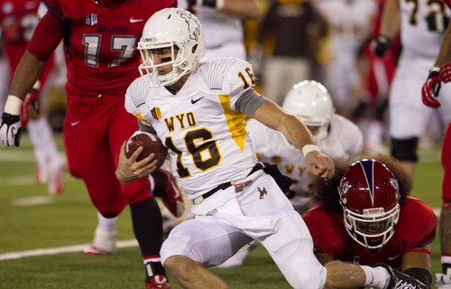 Wyoming quarterback Brett Smith (16) gets tackled by a Fresno St defender Saturday, Nov. 9, 2013 at War Memorial Stadium in Laramie, WY. (AP Photo/Jeremy Martin)