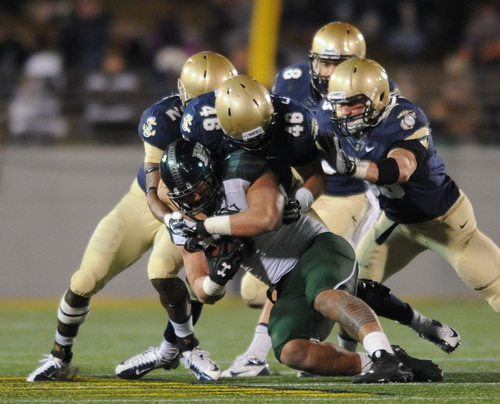 Hawaii's running back Joey Iosefa is tackled by Navy's Will Huntsman in the second half of an NCAA college football game on Saturday, Nov. 9, 2013, in Annapolis, Md. Navy won 42-28. (AP Photo/Gail Burton)