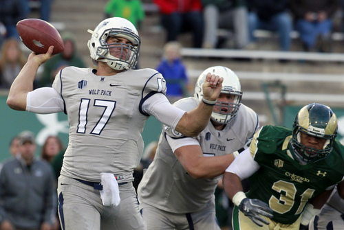 Nevada quarterback Cody Fajardo, left, rolls out to pass the ball as offensive lineman Joel Bitonio, center, blocks Colorado State linebacker Cory James in the fourth quarter of an NCAA college football game in Fort Collins, Colo., on Saturday, Nov. 9, 2013. (AP Photo/David Zalubowski)