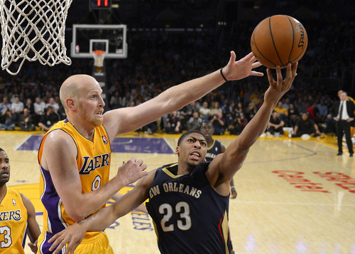 New Orleans Pelicans forward Anthony Davis, right, puts up a shot as Los Angeles Lakers center Chris Kaman defends during the second half of an NBA basketball game, Tuesday, Nov. 12, 2013, in Los Angeles. (AP Photo/Mark J. Terrill)