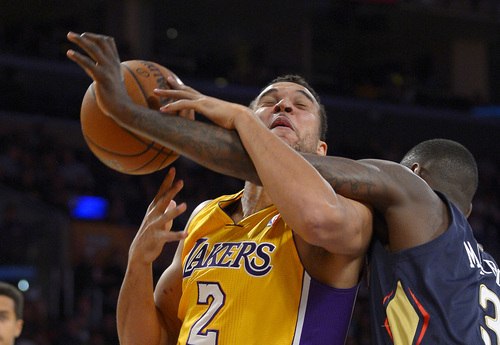Los Angeles Lakers forward Elias Harris, left, of Germany, is fouled by New Orleans Pelicans guard Anthony Morrow defends during the second half of an NBA basketball game, Tuesday, Nov. 12, 2013, in Los Angeles. (AP Photo/Mark J. Terrill)