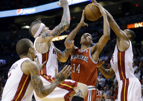 Milwaukee Bucks' Giannis Antetokounmpo (34), of Greece, shoots as Miami Heat's Chris Andersen, second from left, and Rashard Lewis, right, defend during the second half of an NBA basketball game Tuesday, Nov. 12, 2013, in Miami. The Heat won 118-95. (AP Photo/Lynne Sladky)
