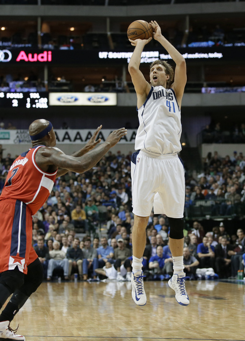 Dallas Mavericks forward Dirk Nowitzki (41) goes up over Washington Wizards' Al Harrington, left, to score a 3-point basket in the second half of an NBA basketball game, Tuesday, Nov. 12, 2013, in Dallas. With that basket Nowitzki passed Jerry West for 16th place on the NBA's all-time scoring list. The Mavericks won 105-95. (AP Photo/Tony Gutierrez)