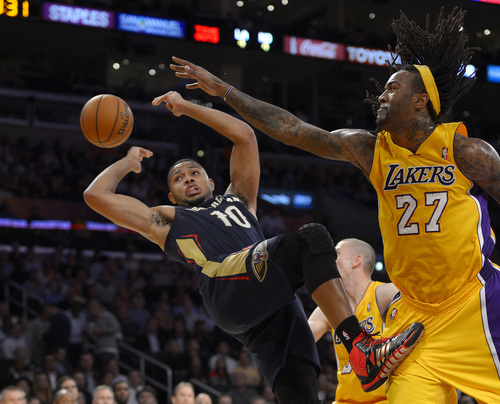 New Orleans Pelicans guard Eric Gordon, left, awkwardly passes the ball behind him as Los Angeles Lakers center Jordan Hill defends during the first half of an NBA basketball game, Tuesday, Nov. 12, 2013, in Los Angeles. (AP Photo/Mark J. Terrill)