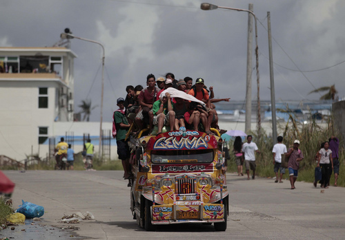 Survivors ride an overloaded passenger jeepney as they flee typhoon-hit Tacloban city, Leyte province, central Philippines on Wednesday, Nov. 13, 2013. Typhoon Haiyan, one of the strongest storms on record, slammed into six central Philippine islands on Friday leaving a wide swath of destruction. (AP Photo/Aaron Favila)