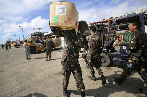 A Philippine soldier carries relief goods delivered in the airport Wednesday, Nov. 13, 2013 in Tacloban city, Leyte province, central Philippines. Typhoon Haiyan, one of the strongest storms on record, slammed into six central Philippine islands on Friday leaving a wide swath of destruction. (AP Photo/Wong Maye-E)