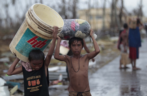 Survivors carry clothes along a road at typhoon-ravaged Tacloban city, Leyte province, central Philippines on Tuesday, Nov. 12, 2013. Four days after Typhoon Haiyan struck the eastern Philippines, assistance is only just beginning to arrive. (AP Photo/Aaron Favila)
