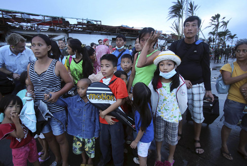 Survivors of Typhoon Haiyan wait at the airport in hopes of being evacuated on C-130 cargo planes, Tuesday, Nov. 12, 2013 in Tacloban city, Leyte province, central Philippines. Four days after Typhoon Haiyan struck the eastern Philippines, assistance is only just beginning to arrive. (AP Photo/Wong Maye-E)