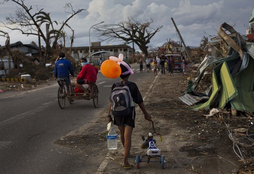 Typhoon Haiyan survivors walk through the ruins of their neighborhood on the outskirts of Tacloban, Philippines on Wednesday, Nov. 13, 2013. Typhoon Haiyan, one of the most powerful storms on record, hit the country's eastern seaboard on Friday, destroying tens of thousands of buildings and displacing hundreds of thousands of people.  (AP Photo/David Guttenfelder)