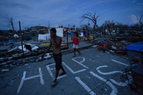 Typhoon Haiyan survivors walk through the ruins of their neighborhood in Tacloban, central Philippines on Wednesday, Nov. 13, 2013. A man named J.R. Apan painted a plea for help in front of his destroyed home the day after the typhoon hit hoping for aid to arrive but says he has not yet received food and water supplies. (AP Photo/David Guttenfelder)