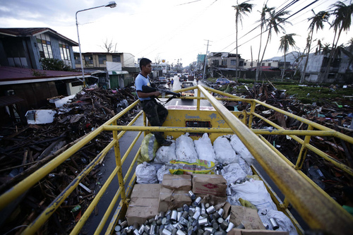 A policeman escorts canned goods after Typhoon Haiyan slammed Tacloban city, Leyte province, central Philippines, Tuesday, Nov. 12, 2013. Four days after Typhoon Haiyan devastated islands in the central Philippines, survivors are desperate for food and clamoring to be evacuated. (AP Photo/Bullit Marquez)