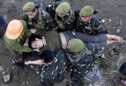 Soldiers rush a typhoon survivor after she collapsed in a queue to board a military transport plane Wednesday Nov. 13, 2013 from the damaged Tacloban airport  in Tacloban city, Leyte province in central Philippines. Typhoon Haiyan, one of the strongest storms on record, slammed into central Philippine provinces Friday, leaving a wide swath of destruction and thousands of people dead. (AP Photo/Bullit Marquez)