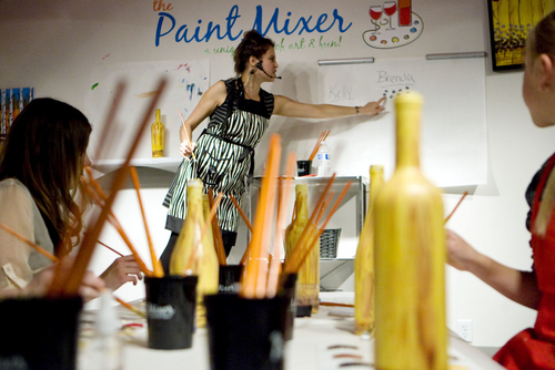 Keith Johnson   The Salt Lake Tribune  Paint Mixer instructor Brenda Hattingh demonstrates a specific step to participants following along and painting a wine bottle at the Paint Mixer location in Salt Lake City, November 7, 2013. Paint Mixer gives participants the opportunity to enjoy a glass of wine or beer, and follow an instructor step-by-step to recreate a featured painting. Paint Mixer has two locations, Sugar House and Park City.