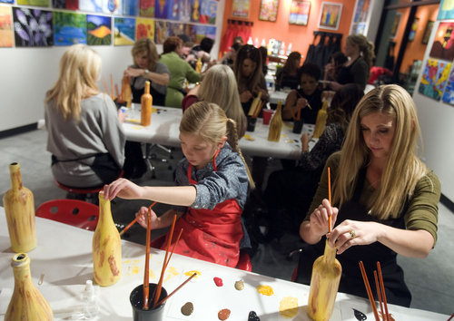 Keith Johnson | The Salt Lake Tribune  Hillary Maxwell (right) and her daughter Makaela (1) paint wine bottles at Paint Mixer in Salt Lake City, November 7, 2013. Paint Mixer gives participants the opportunity to enjoy a glass of wine or beer, and follow an instructor step-by-step to recreate a featured painting. Paint Mixer has two locations, Sugar House and Park City.