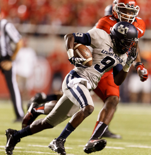 Trent Nelson  |  The Salt Lake Tribune Utah State Aggies wide receiver Bruce Natson (9) is chased down by Utah Utes defensive end Nate Orchard (8) as the University of Utah hosts Utah State, college football Thursday, August 29, 2013 at Rice-Eccles Stadium in Salt Lake City.
